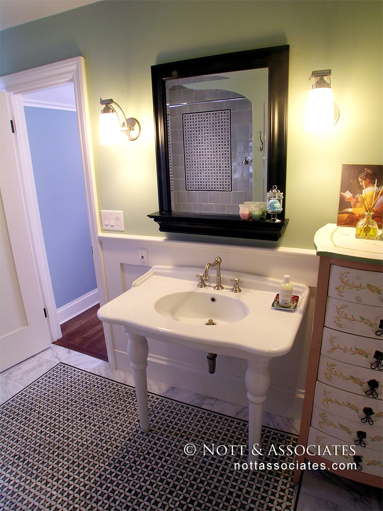 A period style pedestal sink and mosaic pattern floor.