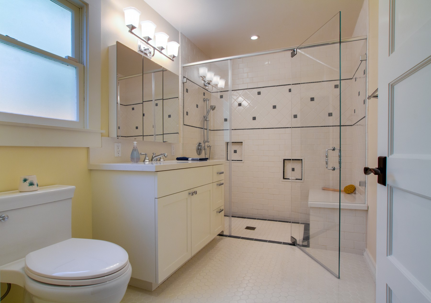 A frameless glass shower for ADA accessibility.