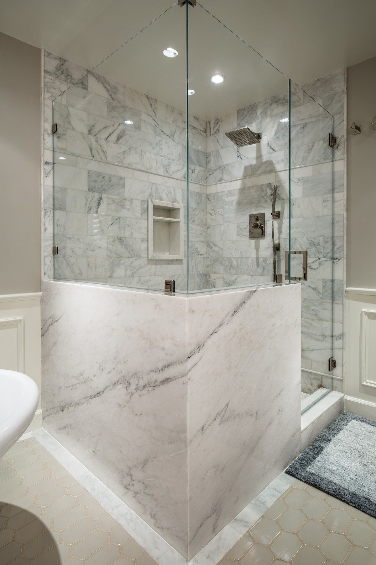 A stone wrapped and frameless glass shower enclosure - Nott & Associates
