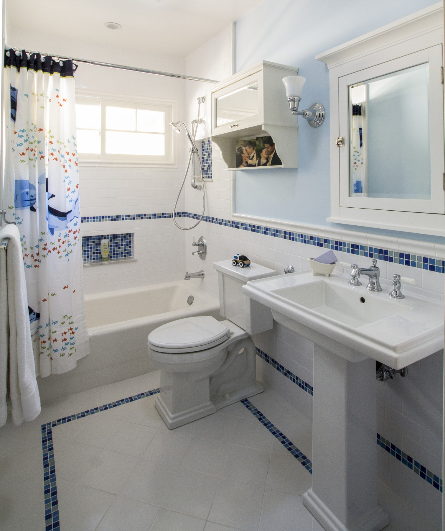 A boys bath with pedestal sink and decorative mosaic tile