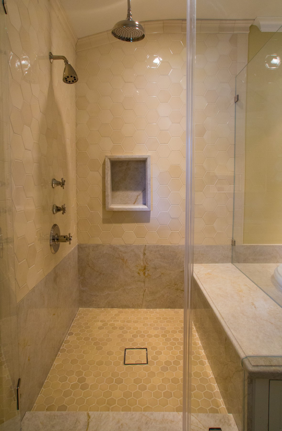 A frameless glass shower with full bench and rain shower head.
