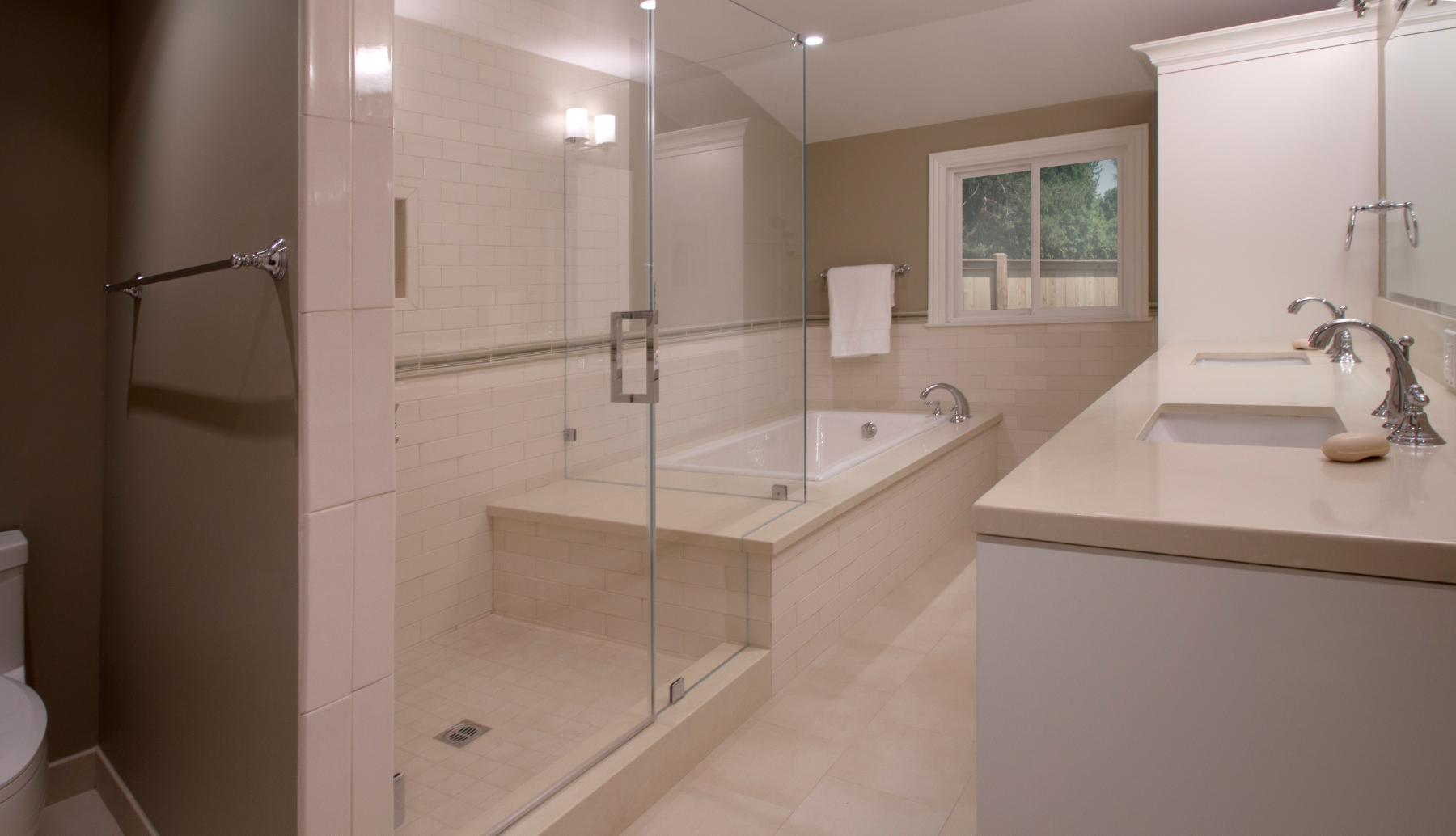 A large frameless glass shower and soaking tub