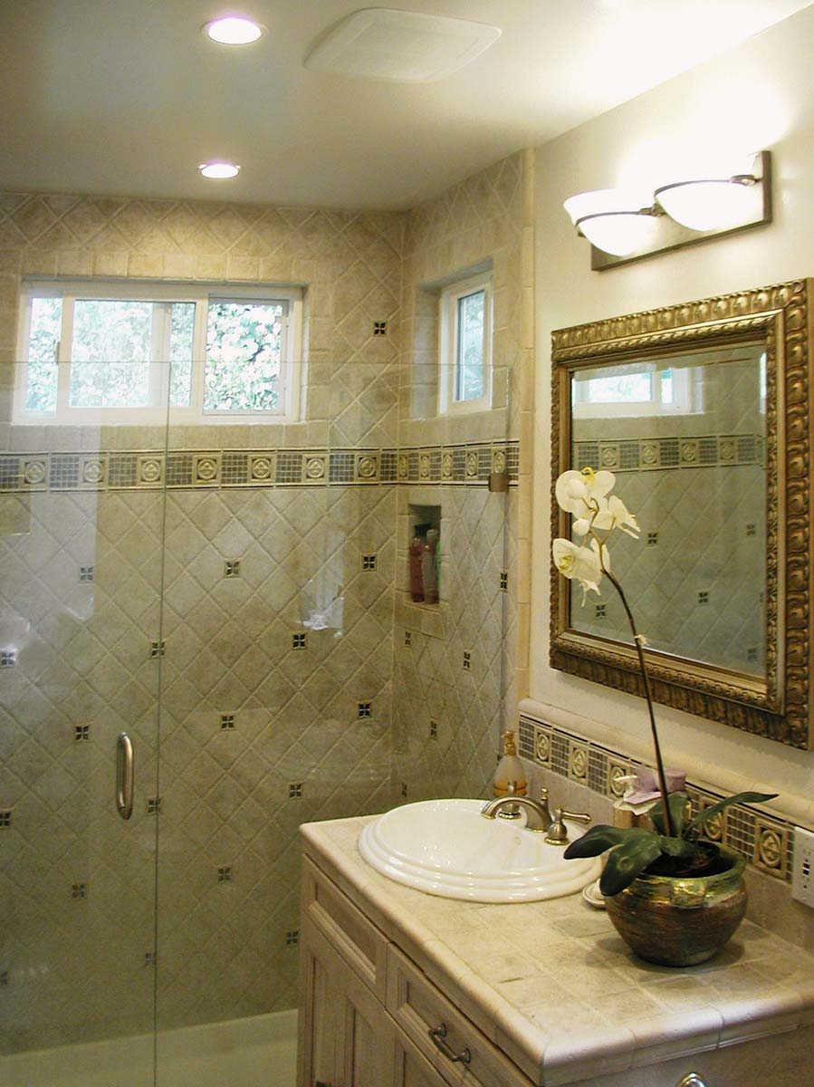 A decorative tiled shower with frameless glass door.