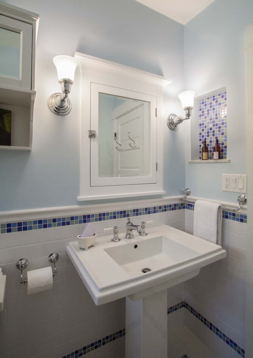 A kid's bath with pedestal sink and decorative mosaic tile