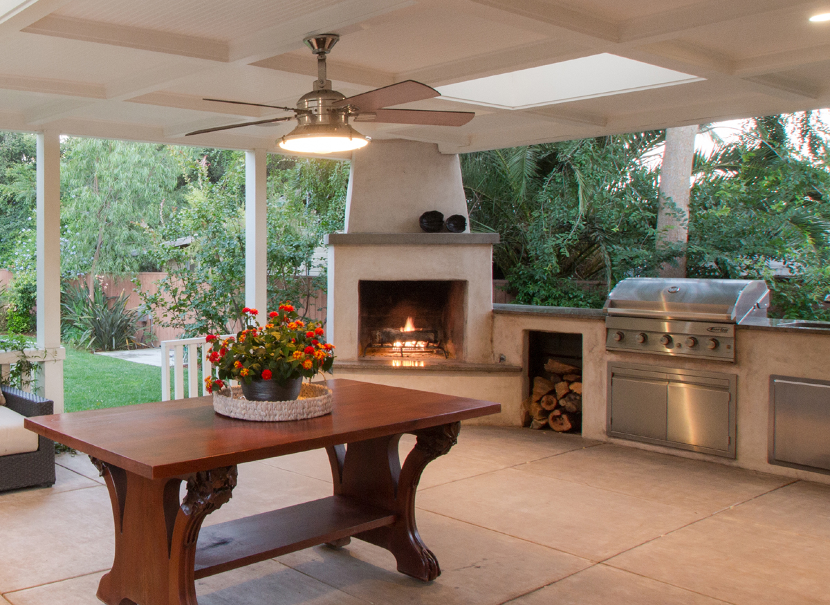 Outdoor entertainment area with wood burning fireplace, BBQ and stone countertops