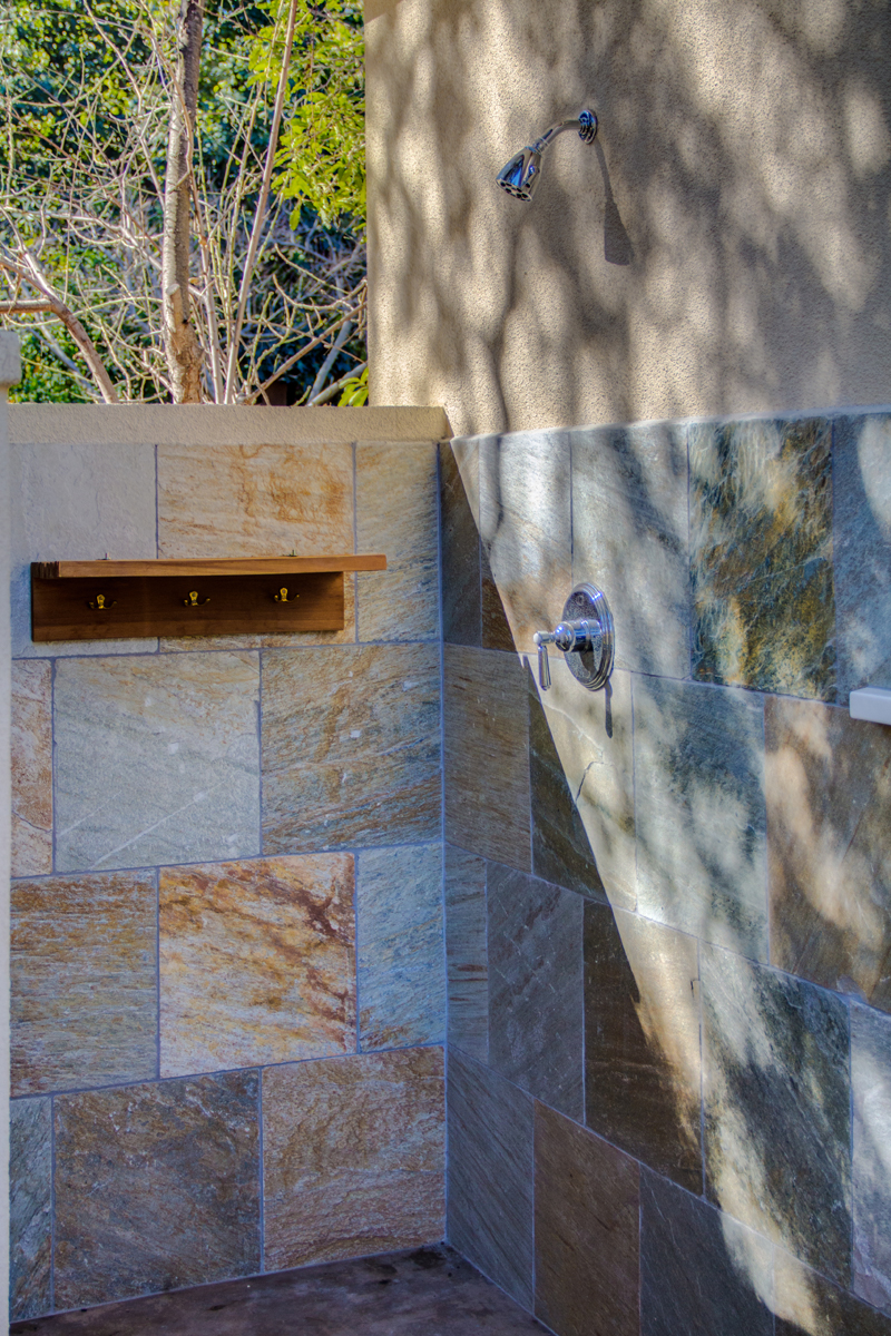 A pool house custom outdoor shower with teak shelf