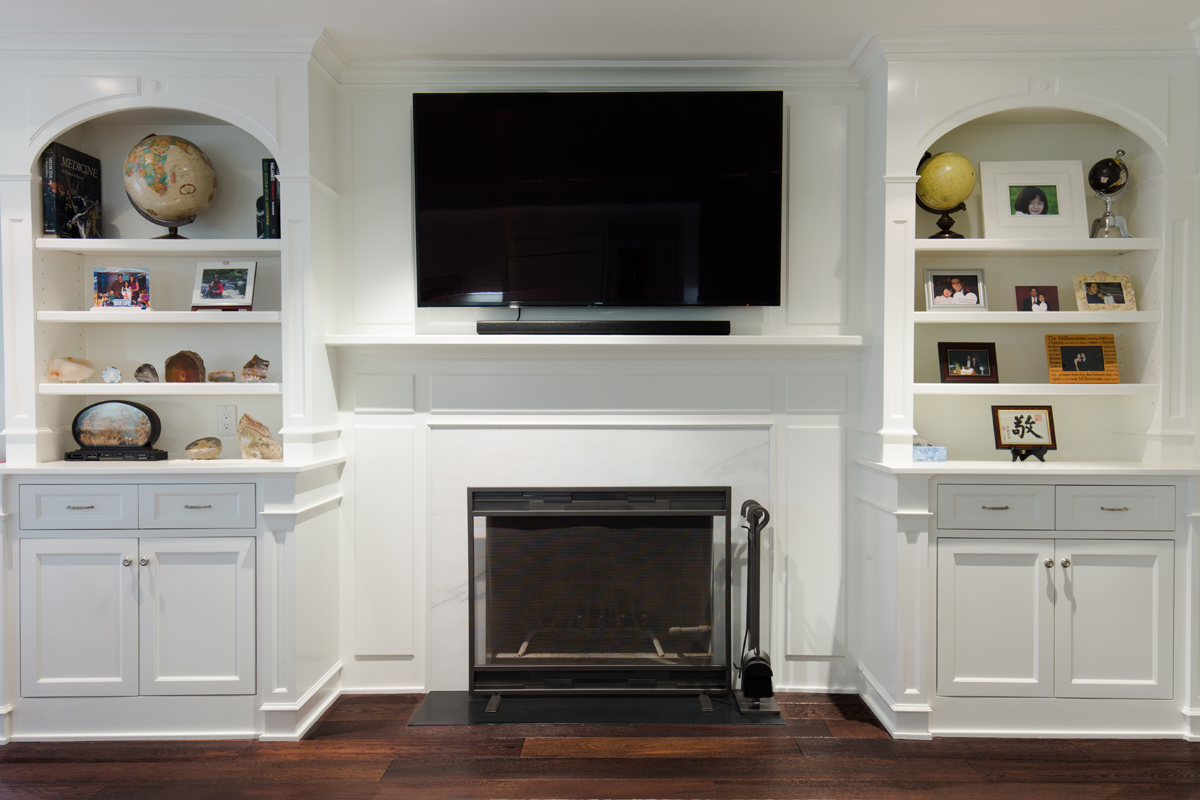 Custom entertainment center over fireplace with flanking bookcases.