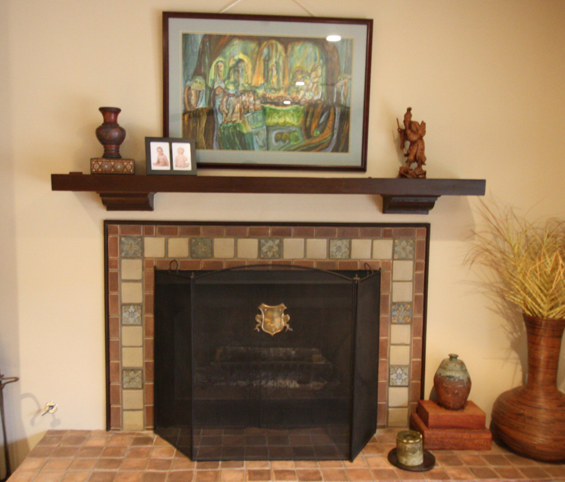 Fireplace with custom tile work and wood mantle.