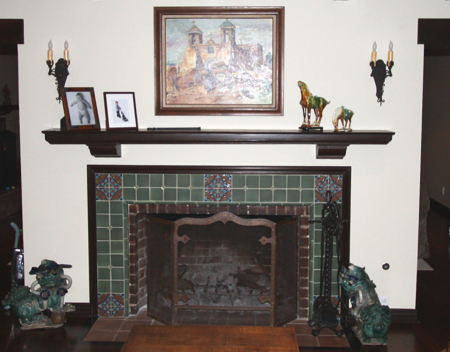 Antique wood burning fireplace with hand-painted tile and custom wood mantle