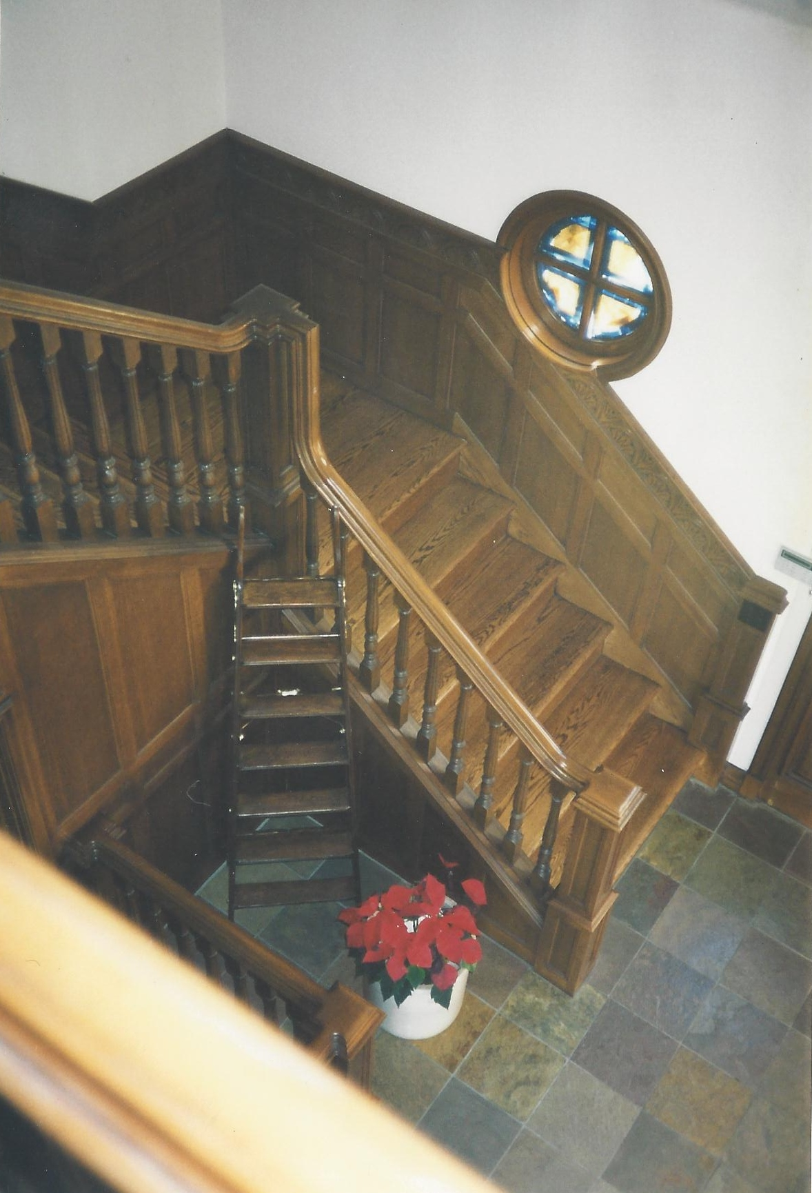 Red oak staircase with wood wainscoting and balustrade.