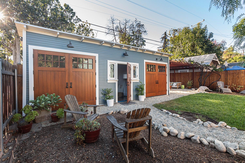Restored Craftsman garage with garden setting.