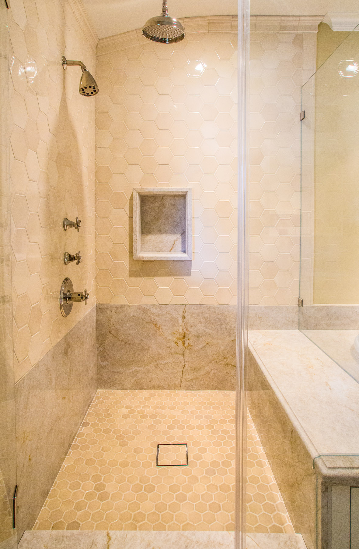 A Frameless Glass Shower With Full Bench And Rain Shower Head-
